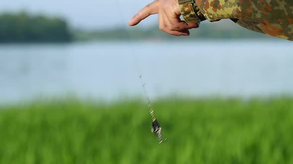 Fisherman Holds a Bait and a Bait on the Line, They Shine