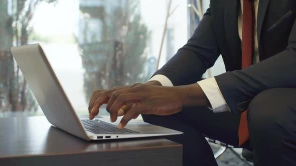 Thumbnail for Hands of Black Businessman Typing on Laptop