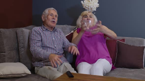Thumbnail for Elderly Family Suddenly Frightened and Throwing Popcorn Bowl While Watching Frightening Movie