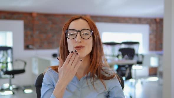 Thumbnail for Porträt redhead Frau zeigt Kuss bei Arbeitsplatz
