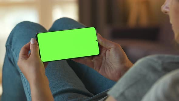 Thumbnail for Woman at Home Lying on a Sofa and Using Smartphone with Green Mock-up Screen in Horizontal Mode