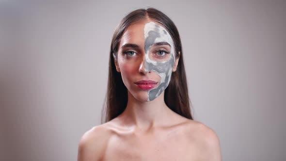 Lächelnd junges Mädchen mit Ton Maske auf halbem Gesicht