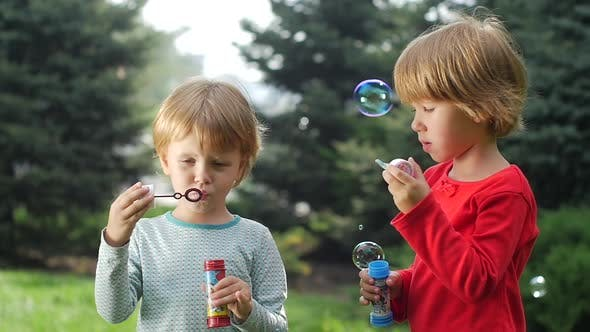 Thumbnail for Two Beautiful Sisters Are Blowing Bubbles in the Park, Slow Motion. Close Up