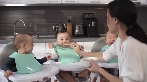 Thumbnail for Filipino Nanny Feeding 1-Year-Old Triplets in High Chairs