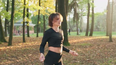 Muscular Brunette Skipping with Jump Rope at Park
