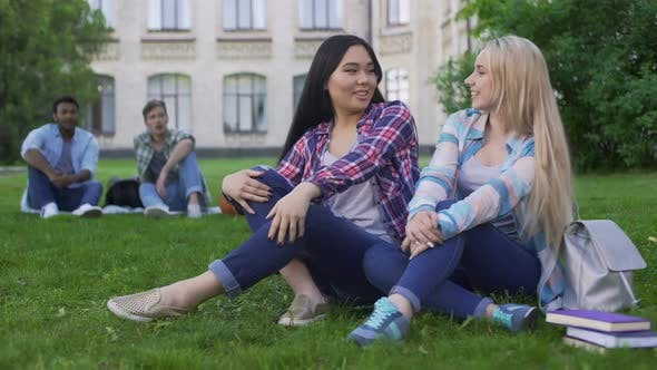 Thumbnail for Females Sitting on Grass, Talking and Smiling, Guys Looking at Girls, Flirt
