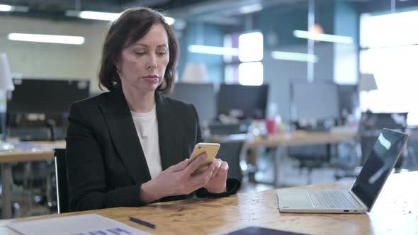 Thumbnail for Cheerful Middle Aged Businesswoman Using Smartphone in Office