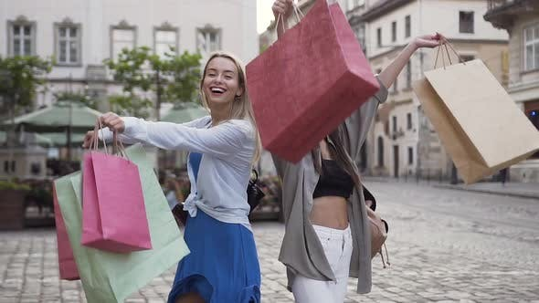 Thumbnail for Lovely Young Smiling Women with Purchases Posing on Camera with Hands Raised