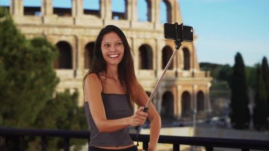 Thumbnail for Cute brunette traveler girl in front of the Roman Coliseum using selfie stick