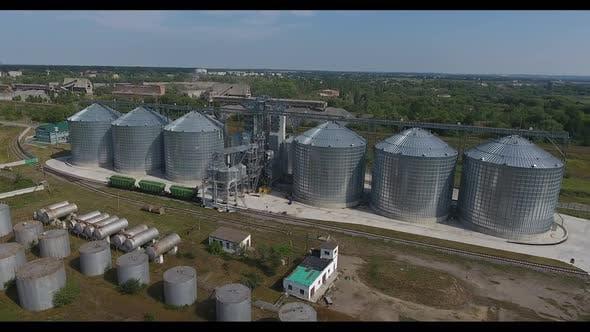 Grain Elevator In Rural Landscape. Modern commercial grain or seed silos in rural landscape
