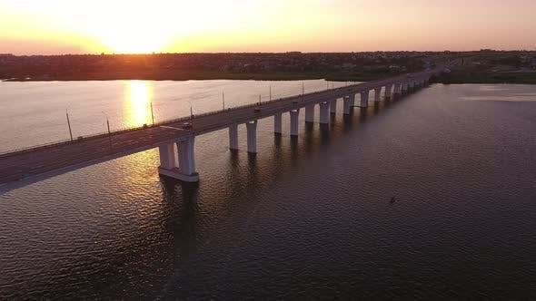 Cover Image for Aerial Shot of a Lengthy Bridge Covering the Dnipro at Splendid Sunset in Summer