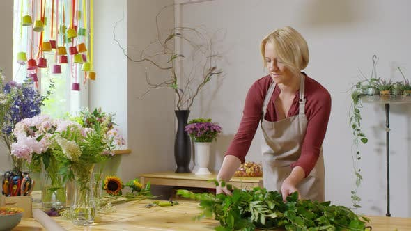 Thumbnail for Florist laying out foliage on table