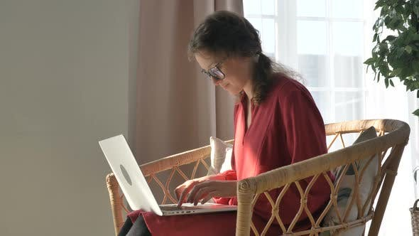 Thumbnail for Pretty Woman in Red Dress Types on Laptop in Rattan Armchair