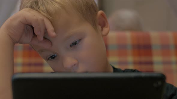Boy spending leisure time with tablet PC