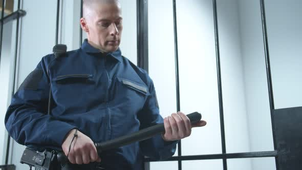 Thumbnail for The Prison Guard Turns a Baton in His Hands