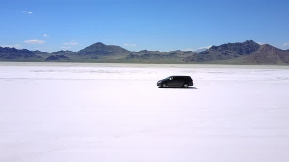 Thumbnail for Drone Follows Modern Minivan Car Moving Along Atmospheric Landscape of Flat Salt Lake Desert
