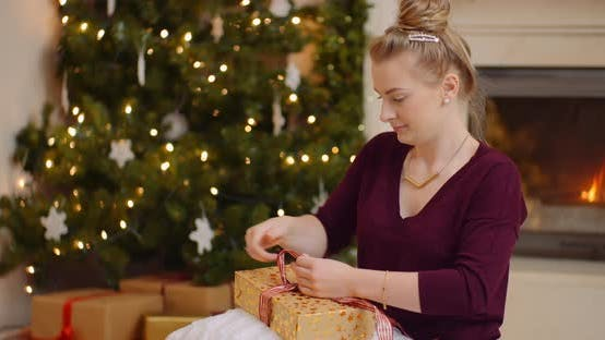 Young Woman Tying Ribbon On Christmas Present