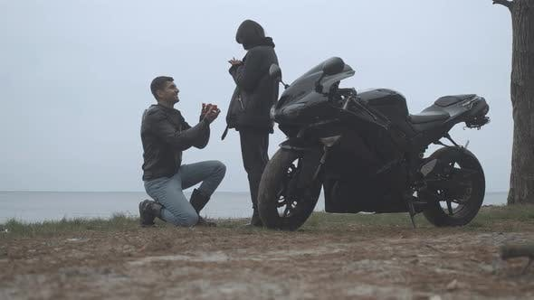 Wide Shot of Happy Boyfriend Proposing To Girlfriend on Cloudy River Bank Outdoors. Happy