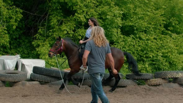 Thumbnail for Young Happy Woman with Long Hair in Blue Shirt Riding a Horse