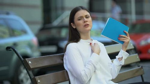 Woman on Bench Waving With Notebook Feeling Sick in Hot Weather Conditions