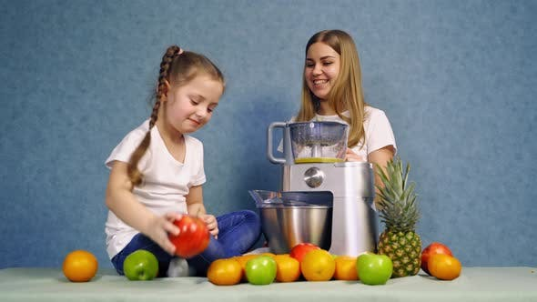 Thumbnail for Woman making fruit smoothie. Beautiful smiling girl with fruits and blender near table