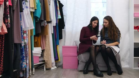 Thumbnail for Beautiful Female Customer Show a Dress She Wants To Order To Boutique Owner Using Cell Phone