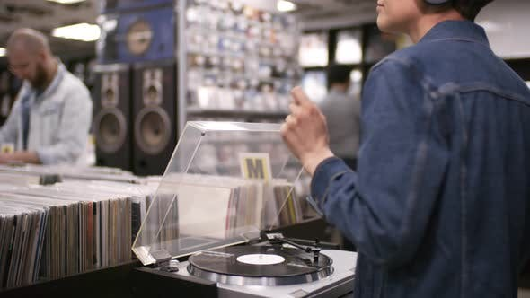 Thumbnail for Woman Listening to Vinyl on Turntable in Record Shop and Swaying to Music