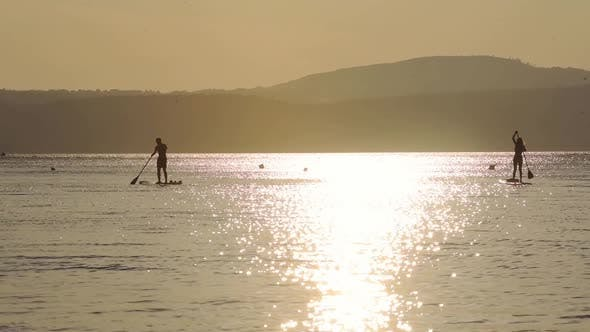 Silhouette Of Couple Doing Stand-up Paddle Board Surfing On The Calm Ocean In Italy With Beautiful R
