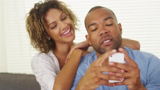 Thumbnail for Black girlfriend watching over boyfriend's shoulder as he texts
