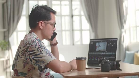 Asiatischer Herausgeber, der auf dem Mobiltelefon mit Videobearbeitungs-App/Software auf seinem Laptop spricht