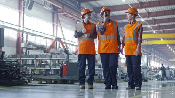 Thumbnail for Female Engineer Talking on Radio Set while Supervising Factory with Colleagues