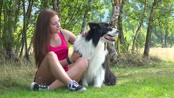 Thumbnail for A Young Beautiful Woman Sits on Grass in a Meadow with a Border Collie, Pets and Hugs It with Smile