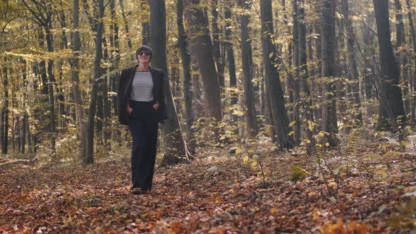Thumbnail for Stylish Young Woman in Jacket and Jeans Walking in the Autumn Park Alone