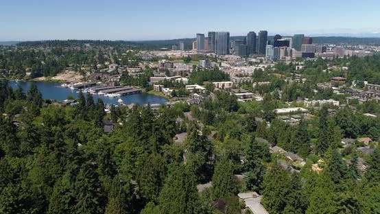 Flying Away From Bellevue Washington Downtown Skyline Above Forest
