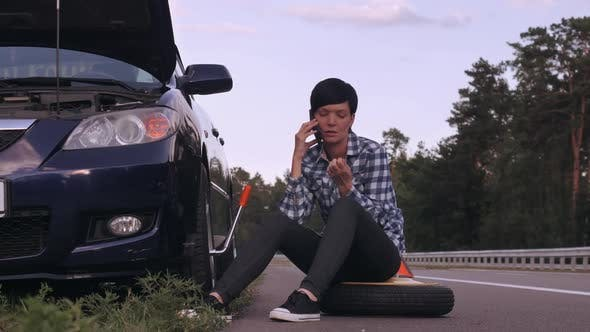 Thumbnail for Driver Try To Change a Tire Outdoors Using Smartphone