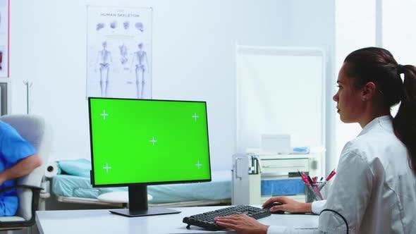 Doctor Using Computer with Green Screen Display
