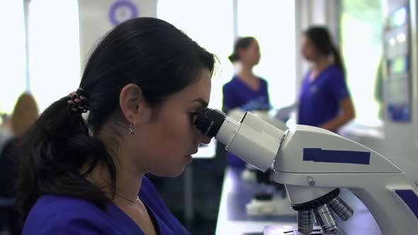 Thumbnail for Young Pretty Woman Doing Analysis in the Laboratory Using Microscope Close Up. The Lady Looking