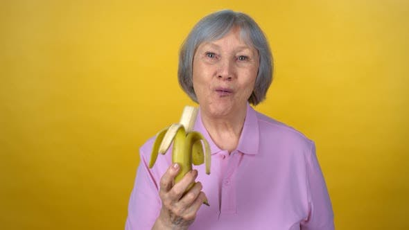 Thumbnail for Cheerful Elderly Woman Eating Banana