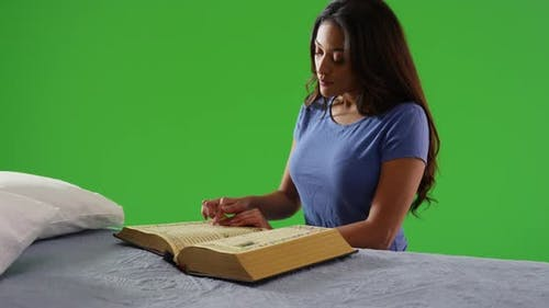 Woman sitting, reading religious text with serene expression on green screen