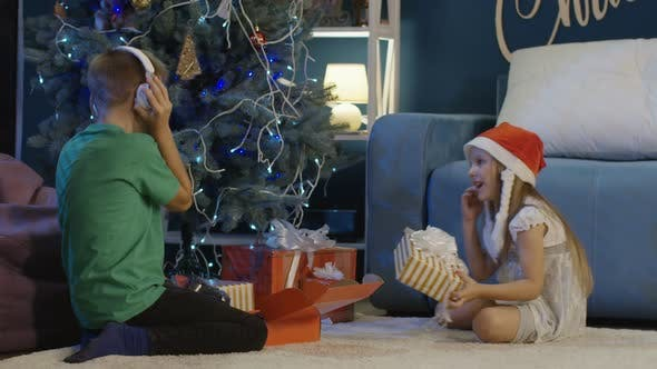 Thumbnail for Happy Kids Unwrapping Christmas Gifts at Home