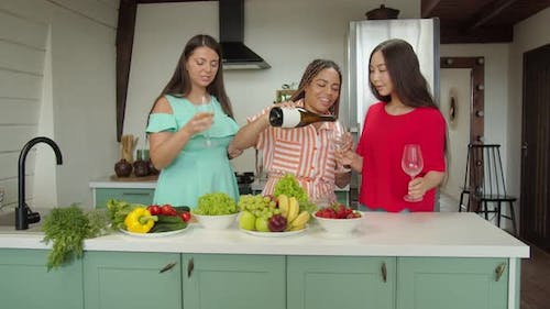 Multiracial Females Pouring Wine Clinking and Enjoying Party at Home
