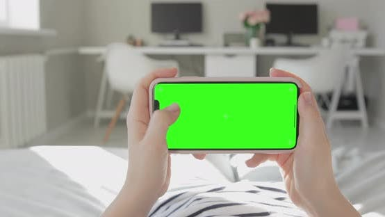 Thumbnail for Woman at Home Office Lying on a Couch Using Green Mock-up Screen iPhone Xs Max. Varied gestures