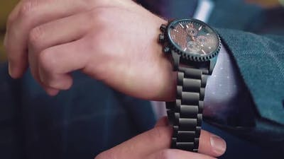 Young Businessman Wears a Wristwatch