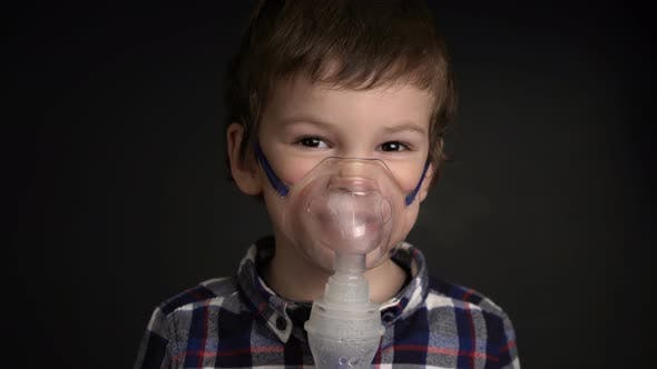Thumbnail for Footage Young Boy Inhaling Through Inhaler Mask