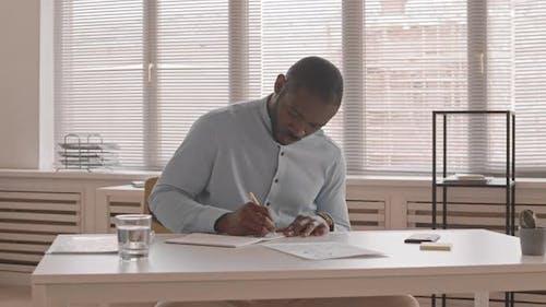 African Man Writing at Desk
