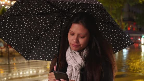 Thumbnail for Millennial caucasian woman using smartphone at night during a rainstorm