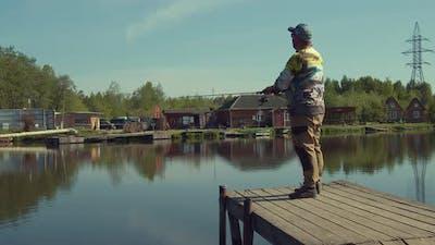 Man Fishing on Wooden Pier Near Lake