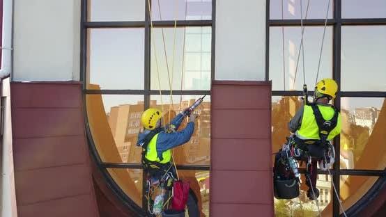Men Washing Windows at Height Modern Skyscraper