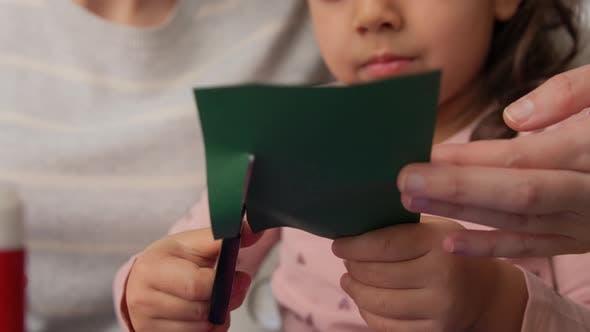 Thumbnail for Mutter und Kind schneiden Farbpapier mit Schere