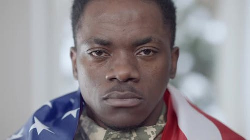 Headshot of Confident Brave African American Soldier Posing at Home with USA Flag